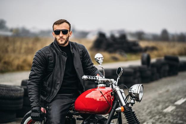 Czerwony motocykl z jeźdźcem. mężczyzna w czarnej skórzanej kurtce i spodniach stoi bokiem na środku drogi. opony są układane w tle