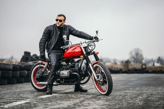 Czerwony motocykl z jeźdźcem. mężczyzna w czarnej skórzanej kurtce i spodniach stoi bokiem na środku drogi.