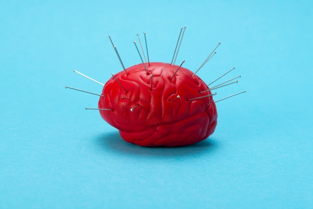 Czerwony mózg na niebieskim tle z wstrzykiwanymi igłami.