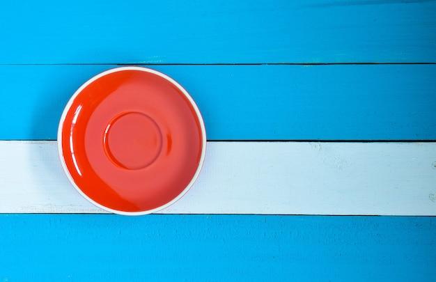 Czerwony naczynie na błękitnym drewnianym tle