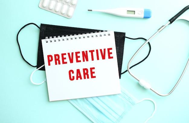 Czerwony napis zapobiegawcza jest napisany na notatniku, który znajduje się na niebieskim tle obok materiałów medycznych.
