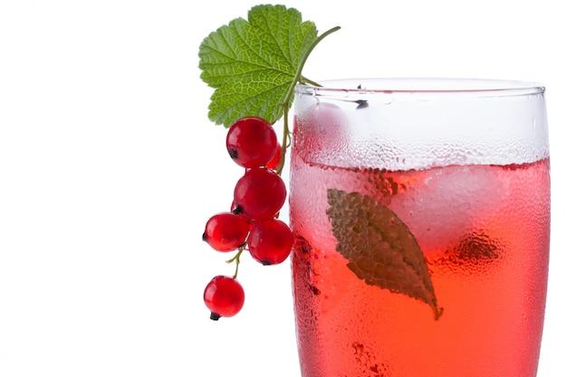 Czerwony napój lub koktajl w szkle dla szampana odizolowywającego na bielu z czerwoną porzeczką