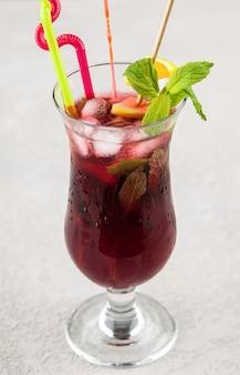 Czerwony napój owocowy w szklance z miętą i cytryną