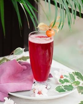 Czerwony napój z pianką i kwiatem jagodowym.