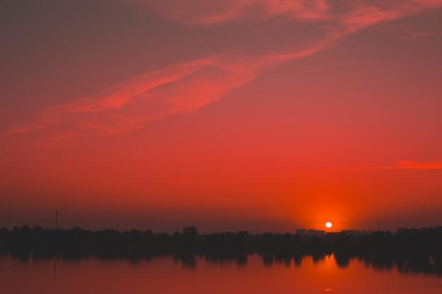 Czerwony nasycony zachód słońca nad rzeką