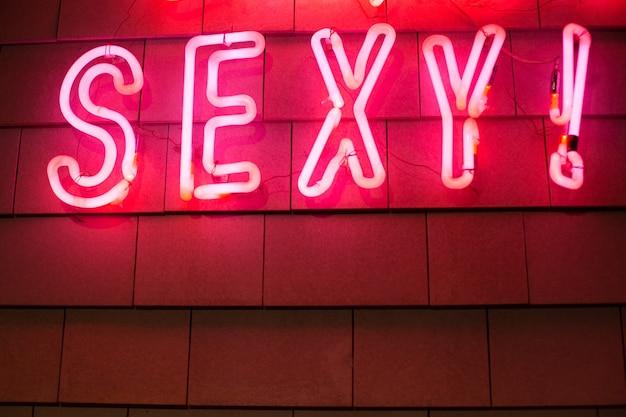 Czerwony neon jest gorący, kiedy trzęsę się na czarnym tle modna koncepcja lat 80.