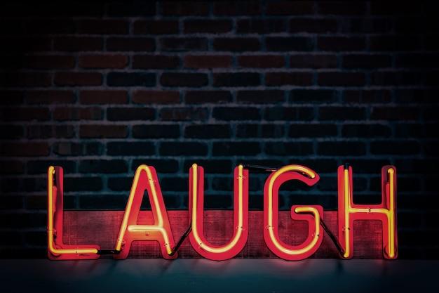 """Czerwony neon z napisem """"śmiej się"""" na ciemnym tle ceglanego muru"""