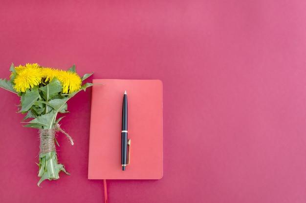 Czerwony notatnik długopis i bukiet żółtych dmuchawców