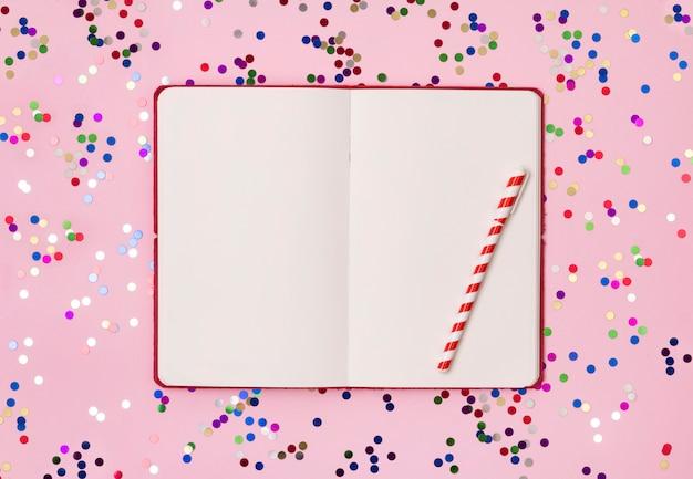 Czerwony notatnik z kolorowymi konfetti na różowym tle. leżał płasko, widok z góry