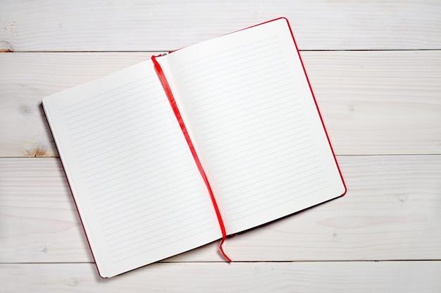 Czerwony notes do codziennych notatek na białej drewnianej powierzchni