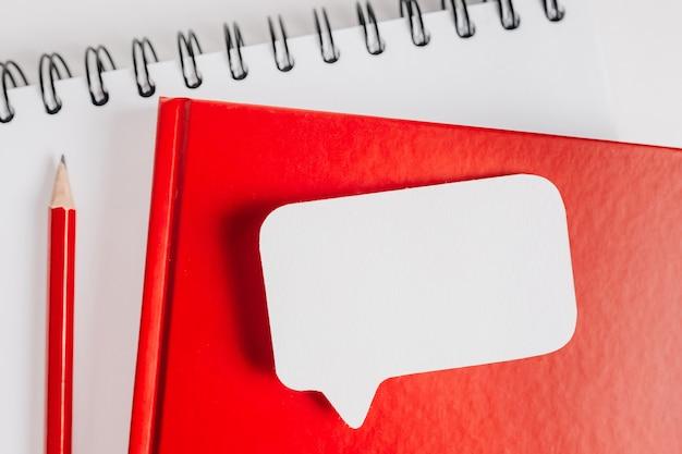 Czerwony notes i biała naklejka na biurku. makiety w tle przestrzeni biurowej. ważne jest, aby nie zapomnieć o notatce