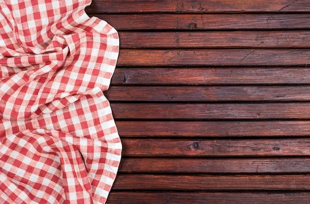 Czerwony obrus w kratkę na ciemnym drewnianym stole z, widok z góry z miejsca kopiowania
