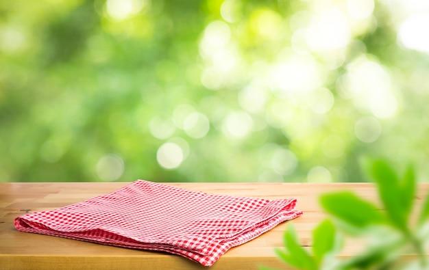 Czerwony obrus w kratkę na drewnie z zielonym bokeh rozmycia drzewa