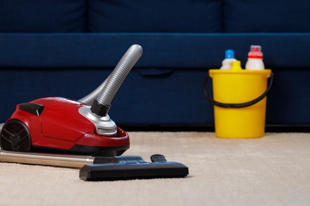 Czerwony odkurzacz na beżowym dywanie