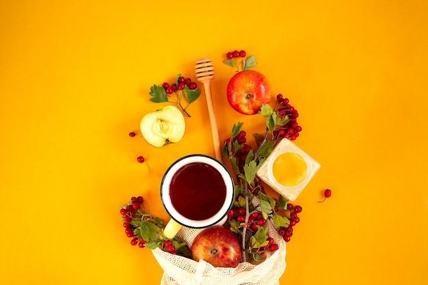 Czerwony ogród ekologiczne jabłka, jagody głogu w siateczkowej torbie i filiżankę gorącej przyprawionej herbaty na pomarańczowym tle. jesień martwa płasko leżała.