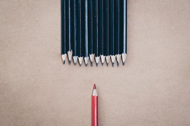 Czerwony ołówek wyróżniający się z tłumu obfitości identycznych czarnych facetów