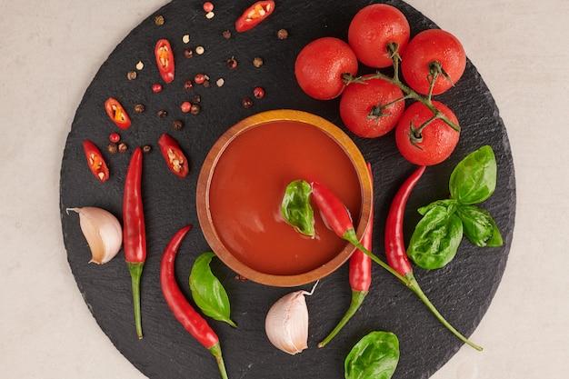 Czerwony ostry sos chili. ketchup pomidorowy, sos chilli, puree z papryczką chili, warzywa, pomidory i czosnek. na powierzchni czarny kamień. widok z góry