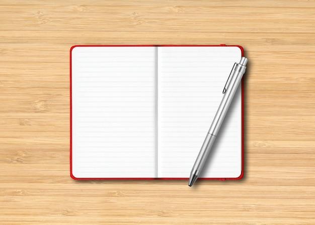Czerwony otwarty notatnik w linie z piórem na białym tle na podłoże drewniane
