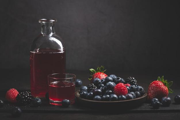 Czerwony owoc sok z jagodami na ciemnym tle