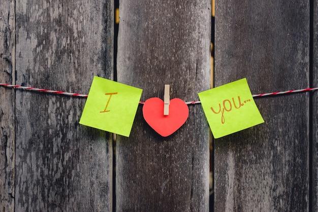 Czerwony papier w kształcie serca i słowa miłości