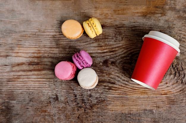 Czerwony papierowy kubek z kawą i makaronikami na drewnianym tle. kawa na wynos z miejscem na kopię