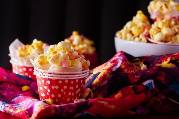 Czerwony papierowy kubek z popcornem na pomarańczowo