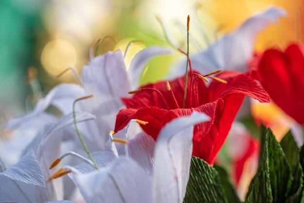 Czerwony papierowy kwiat wśród białych kwiatów