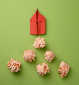 Czerwony papierowy samolot i zmięte papierowe kulki na zielonym tle, widok z góry. koncepcja znajdowania innowacyjnych pomysłów, właściwych rozwiązań. eliminacja błędów i skok do przodu dla lidera