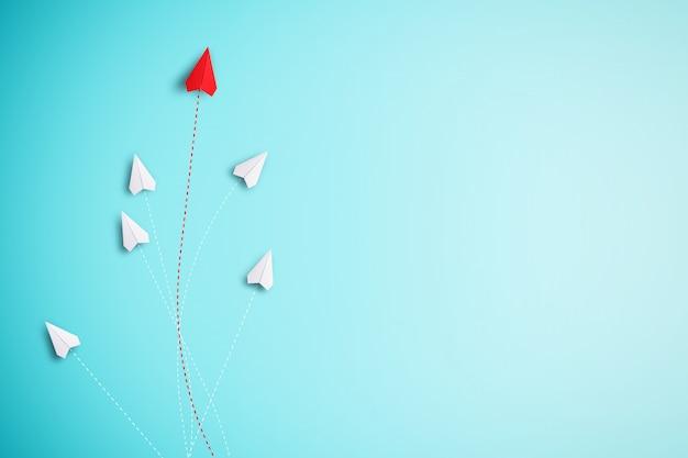 Czerwony papierowy samolot poza linią z białym papierem, aby zmienić zakłócenie i znaleźć nowy normalny sposób na niebieskim tle.