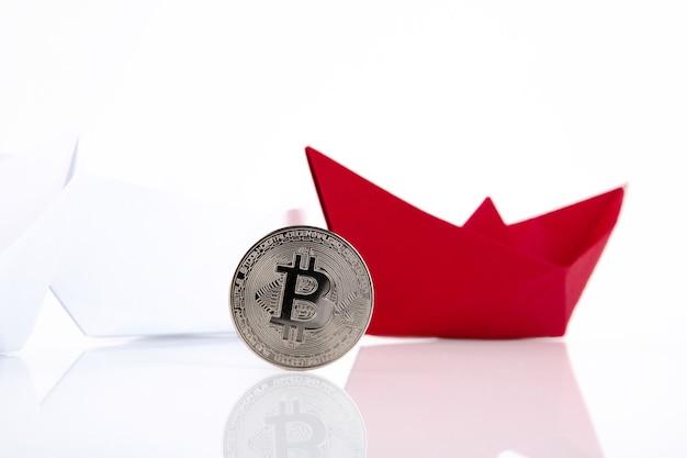 Czerwony papierowy statek, bitcoin platynowy na białej powierzchni.