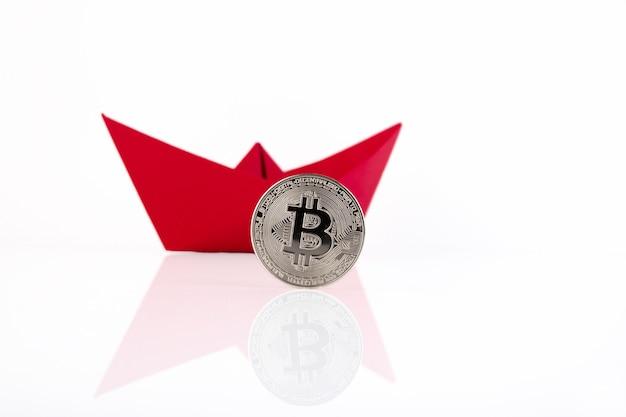 Czerwony papierowy statek, platynowa moneta bitcoin na białym tle