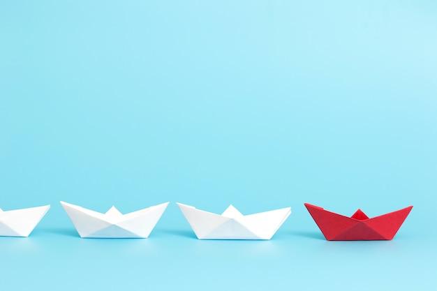 Czerwony papierowy statek prowadzi wśród bielu na błękitnym tle z kopii przestrzenią.