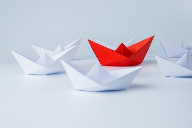 Czerwony papierowy statek prowadzi wśród bielu
