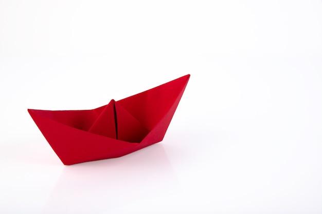 Czerwony papierowy statek z papieru na białym tle