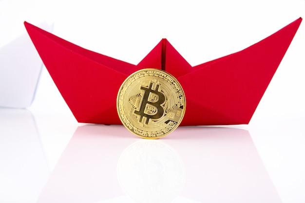 Czerwony papierowy statek, złote bitcoiny na białym tle