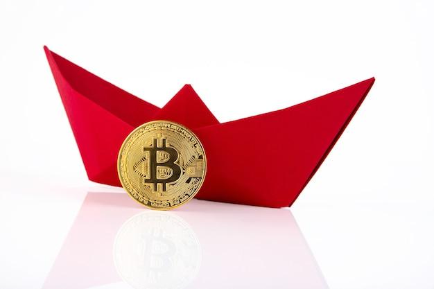 Czerwony papierowy statek, złote monety bitcoin na białym tle