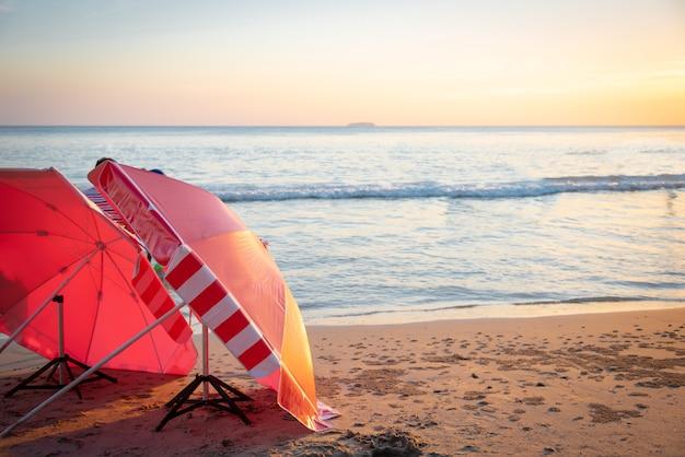 Czerwony parasol na plaży wśród zmierzchu na morzu.