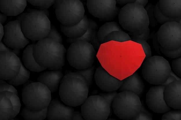 Czerwony parasol w kształcie serca góruje nad innymi czarnymi parasolami