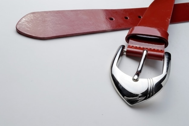 Czerwony pasek damski z chromowaną blaszką na białym tle. zbliżenie.