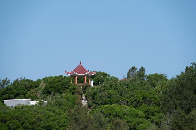 Czerwony pawilon wśród zielonych drzew pod błękitnym niebem