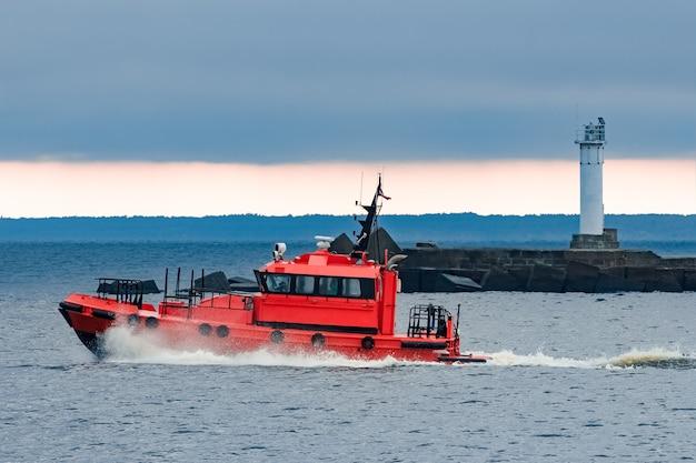 Czerwony pilotujący statek szybko mija latarnię morską w rydze