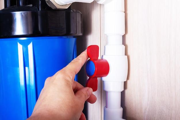Czerwony plastikowy kran na białej fajce wodnej