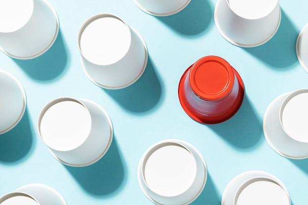 Czerwony plastikowy kubek otoczony papierowymi kubkami