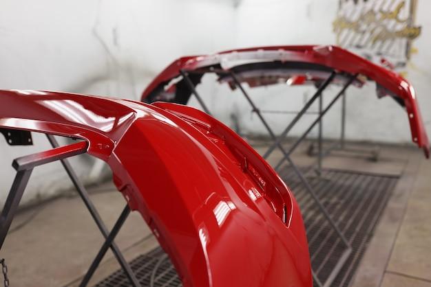 Czerwony plastikowy zderzak samochodowy wysycha po malowaniu w kabinie lakierniczej