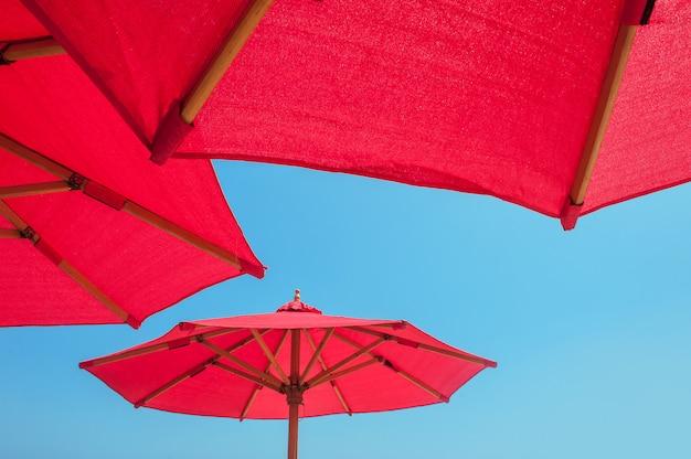 Czerwony plażowy parasol przeciw pogodnemu niebieskiemu niebu
