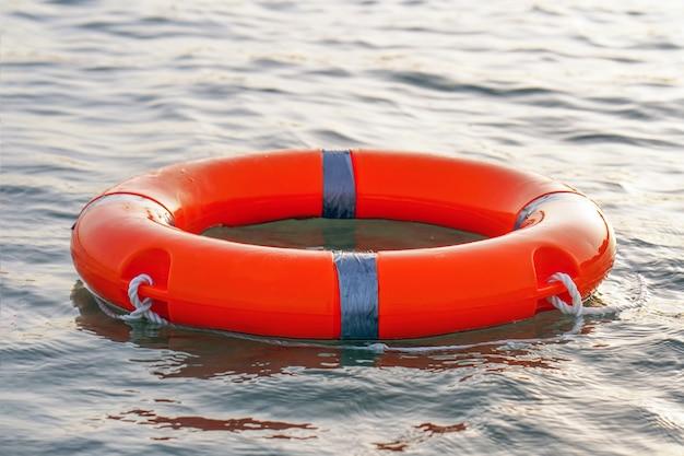 Czerwony pływak koło ratunkowe pływaka
