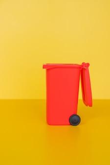 Czerwony pojemnik na śmieci na żółtej ścianie