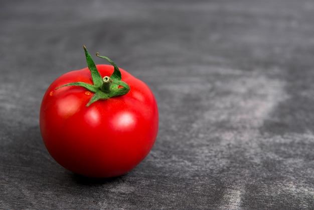 Czerwony pomidor na drewnianym popielatym stole