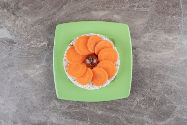 Czerwony pomidor pośrodku plasterków marchwi, a pod talerzem ciasto ryżowe, na marmurowej powierzchni