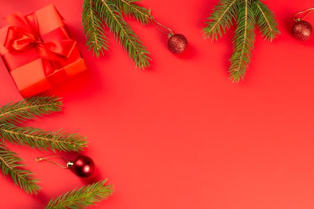 Czerwony prezent, gałęzie świerkowe, czerwone ozdoby na czerwonym tle